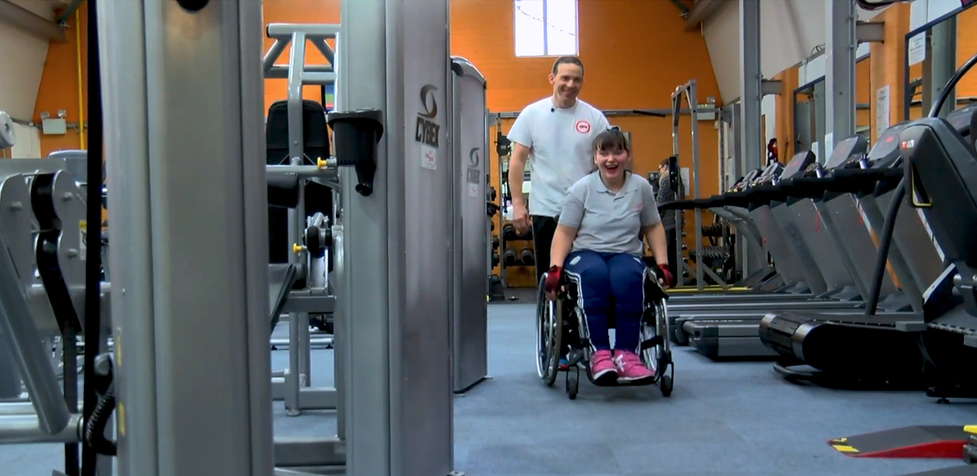 Visually Impaired student and staff member from QAC in the QAC gym